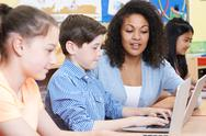 Teacher Helping Male Elementary Pupil In Computer Class Stock Photos