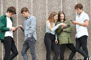 Group Of Teenagers Sharing Text Message On Mobile Phones Stock Photos