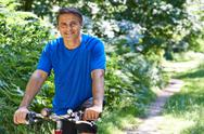 Mature Man Cycling Along Path In Countryside Stock Photos