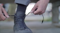 A young man ties his high-top shoes before riding his skateboard. Stock Footage