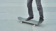 A young man does a trick while riding his skateboard in a town square. Stock Footage