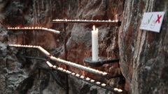 Many small burning candles are on the wall of Finnish Church of the Rock Stock Footage