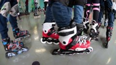 Children feet are booted roller skates stand at start position in skating ring Stock Footage
