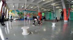 Girls ride on rollerskates under crossbar in skating ring Stock Footage