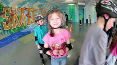 Children a roller skaters are wearing full safety equipment with helmets Stock Footage