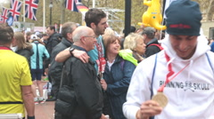 London Marathon competitors with medals mixing with spectators at end of race Stock Footage