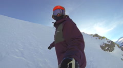 POV shot of a young man snowboarding in the mountains, super slow motion. Stock Footage