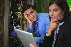 Bored technician looking at colleague while analyzing server Stock Photos