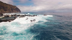 Waves and rocks near city and pools of Porto Moniz aerial view Stock Footage