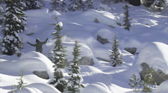 A young man snowboarding over rocks and jumps in the mountains, super slow motio Stock Footage
