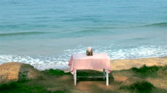 Single dining table in front of the sea Stock Footage