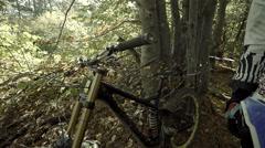 Racer mountain bike downhill puts his helmet on the handlebars Stock Footage