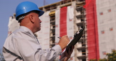 Serious Engineer Inspecting Building Construction Site Take Notes in Work Agenda Stock Footage