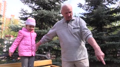 Grandfather playing with granddaughter on park bench Stock Footage