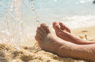 Female feet on the sandy beach over sea in background. Stock Photos