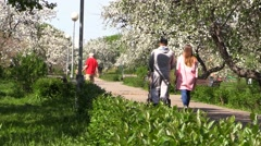 Family People with baby carriage and children play and walk in urban garden Stock Footage