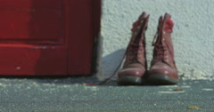 Dusty Old Red Army Boots Lying Outside House Stock Footage