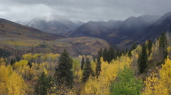 Wide shot of storm clouds over snowy mountains and yellow Autumn aspen trees Stock Footage