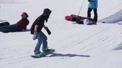 Snowboarder ride on rail on ski resort. Sunny day. Snowy mountains. People Stock Footage