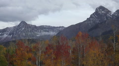 Long shot of snowy mountains and colorful Autumn trees on a cloudy day Stock Footage