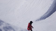 Snowboarder ride on slope on ski resort. Sunny day. Snowy mountains. Extreme Stock Footage