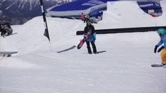 Snowboarder in helmet slide on rail on ski resort. Sun. Snowy mountains. People Stock Footage