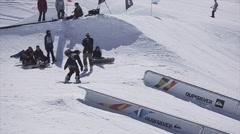 Snowboarder slide on rail on ski resort. Make stunt. Sunny day. Snowy mountains Stock Footage