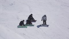 Snowboarders sitting on slope on ski resort. Sun. Snowy mountains. Extreme sport Stock Footage