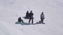 Snowboarders on slope on ski resort. Sunny day. Snowy mountains. Riding Stock Footage