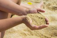 Sand in the woman hands on the beach. Stock Photos