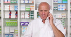Pharmacist Working in a Drugstore Talking on the Phone with a Client About Pills Stock Footage