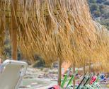 Sand beach with straw sunshades , summer travel vacation. Stock Photos