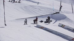 Snowboarder make backslide on rail. Ski resort. Sunny. Mountains. Cameraman Stock Footage