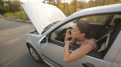 Woman with broken down car calling for help Stock Footage