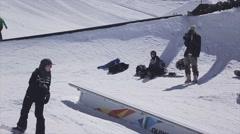 Snowboarder slide on rail. Ski resort. Sunny. Extreme stunts. Active sport Stock Footage