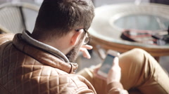 Back look of man sitting in cafe and using phone. 4K Stock Footage