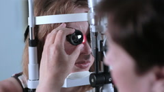 Female Doctor checking eyes with modern medical device. Eye examining at modern Stock Footage