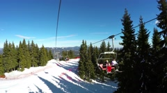 Chair ski lift with skiers going over the mountain and ski tracks at Pamporovo Stock Footage