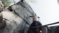 Man climbing on cliffed rock belay Stock Footage