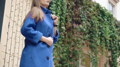 Fashionable girl looking aside in blue coat on the street 4K Stock Footage