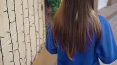 Cute girl looking aside in blue coat on the street 4K Stock Footage