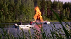 People in small boats watching a midrummer pyre in Finland on Midsummer Eve Stock Footage
