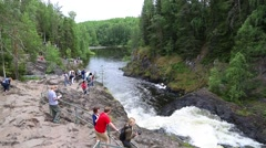 People relax in the famous Kivach waterfall in Russia Stock Footage