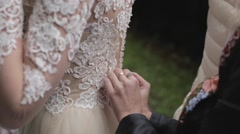 Female hands are buttoning the bride's dress. Stock Footage