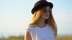 Young beautiful woman model in hat and sunglasses posing outdoor Stock Footage