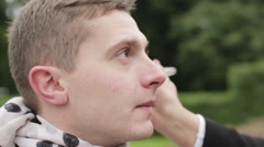 Female hand with a brush applying makeup on the face of a man outdoors. Stock Footage