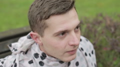Close-up. Young attractive man is looking forward sitting in a park. Stock Footage