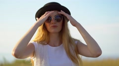 Young beautiful woman model in hat and sunglasses posing and smiling outdoor Stock Footage
