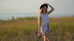 Young beautiful model in hat posing on the edge of a cliff near the river Stock Footage