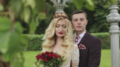 Bride and groom are posing in the park among decorations of flowers and plants. Stock Footage